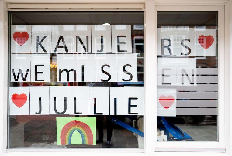 Op het raam van een kinderdagverblijf staat de tekst