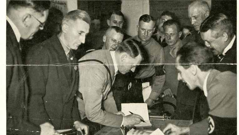 Adolf Hitler signeert een exemplaar van zijn boek. Geheel rechts propagandachef Joseph Goebbels Beeld Mac Evans