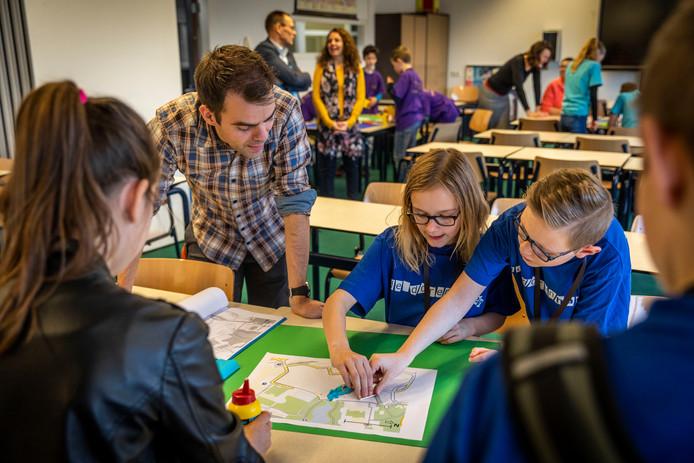 Veertien teams van scholen uit de regio strijden in de allereerste GEObattle van het Were Di. Aardrijkskundedocent Robert Janssen helpt de kinderen.