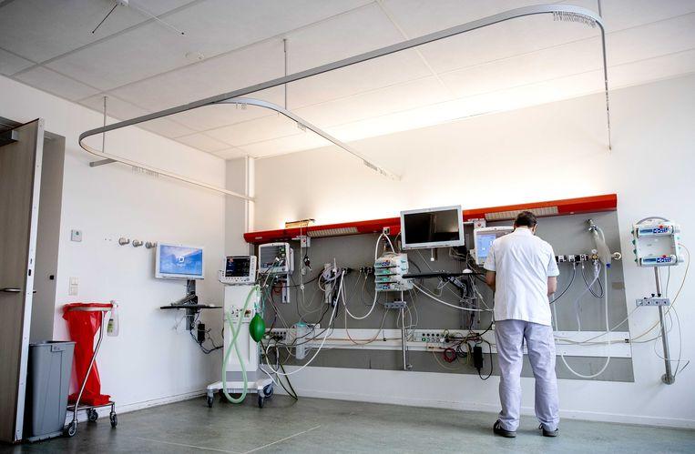 Een medewerker treft voorbereidingen in een extra intensive care-kamer in het Tergooi ziekenhuis. In de kamer kunnen vier coronapatiënten opgenomen worden.  Beeld ANP