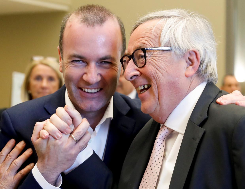 Spitskandidaat Manfred Weber (links) schudt de handen met Jean-Claude Juncker, de huidige voorzitter van de Europese Commissie.