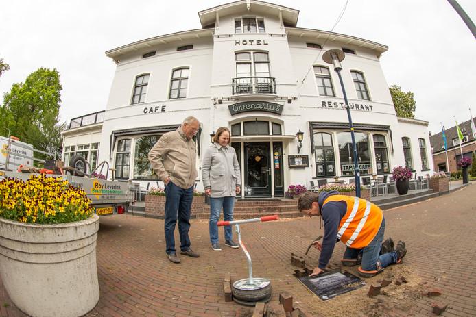 Stratenmaker Roy Leverink legt de tegels onder toeziend oog van bestuursleden Mooi Ruurlo Ap Schepers en Rina Florijn, op de foto wordt de tegel voor hotel Avenarius aan de Dorpsstraat gelegd.