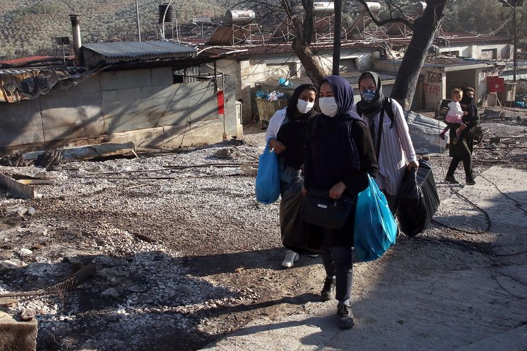 Asielzoekers lopen tussen de puinhopen van kamp Moria op Lesbos, waar gisteren brand uitbrak nadat een groep vluchtelingen die positief getest waren op corona weigerden om in isolatie te gaan.  Beeld EPA