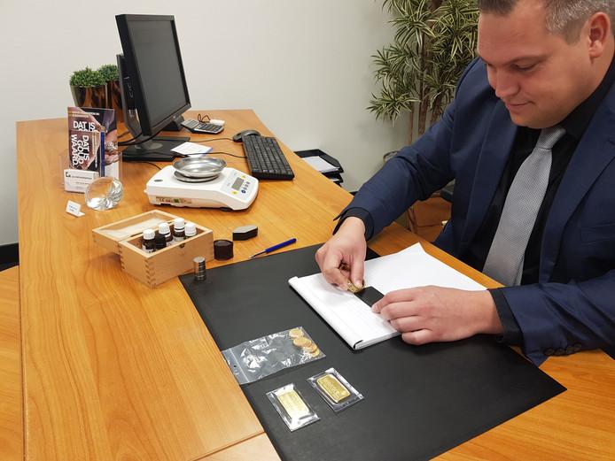 Vestigingsmanager Henk van der Steenhoven van het Goudwisselkantoor in Eindhoven  test het goudgehalte.