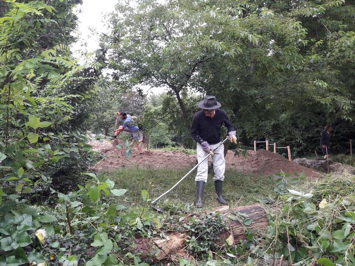 Met zeis en schep aan het werk in de speeltuin in Groenewoud.