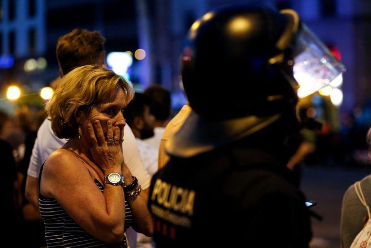 Een politieman tussen de menigte in Barcelona donderdagavond. Beeld AFP