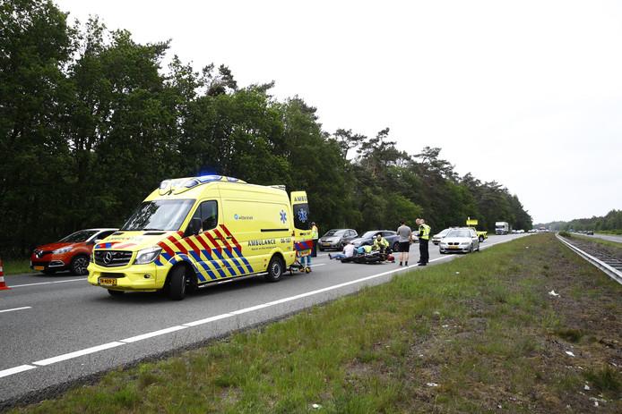 Ambulancepersoneel onderszoekt de motorrijder die op de A50 onderuit is gegaan.