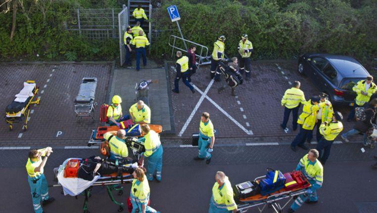 Hulpverleners evacueren gewonde reizigers van de treinen die met elkaar in botsing kwamen. Beeld ANP