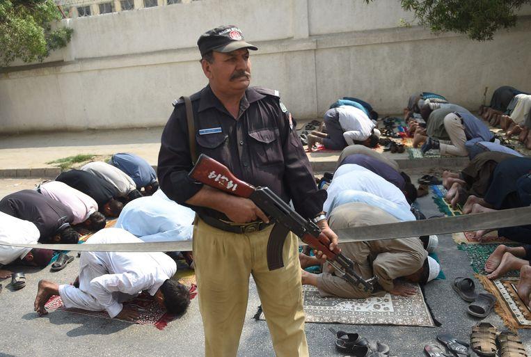 Na de aanslag werd zoals gebruikelijk de bewaking van gelovigen opgevoerd. Hier bewaakt een politieman een groep biddende gelovigen in de grote havenstad Karachi, ook een broeinest van extremisten. Beeld AFP