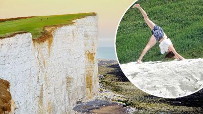 Toeriste doet yoga op afbrokkelende klif