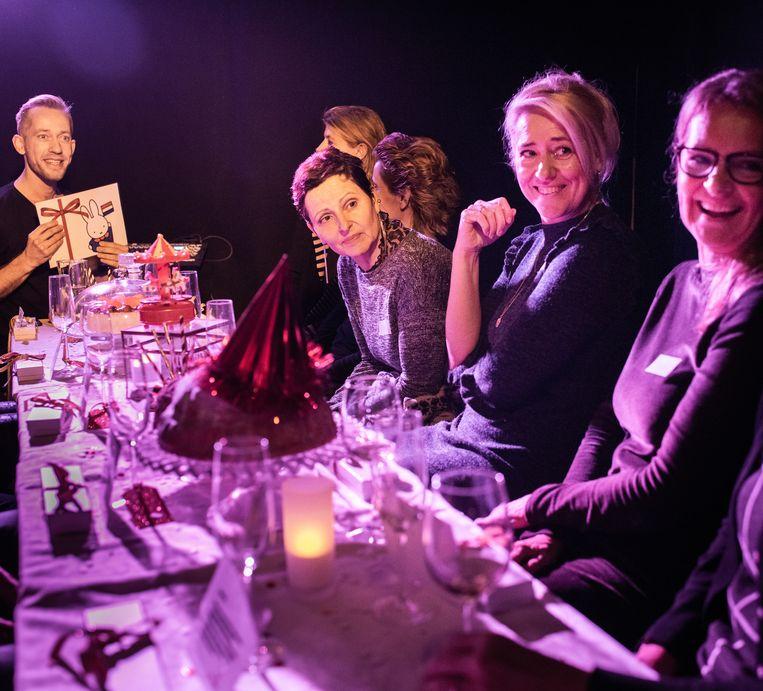 Toeschouwers aan tafel bij zanger en acteur Gerben Grimmius voor zijn korte voorstelling Wat een feest in het TapasTheater. Beeld Simon Lenskens