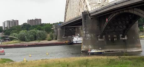 Boot strandt onder Waalbrug, opvarenden zitten vast