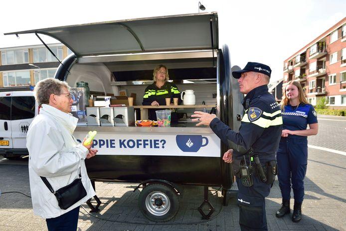 Wijkagent Martin Oost in gesprek met Johanna van den Berg. De politie stond zaterdag in Reeuwijk met een speciale koffiekar.