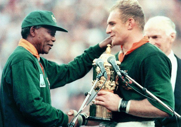 24 juni, 1995: Nelson Mandela, zelf ook in het shirt met rugnummer 6,  feliciteert de Zuidafrikaanse teamcaptain Francois Pienaar met het behalen van de wereldtitel.  Beeld AFP