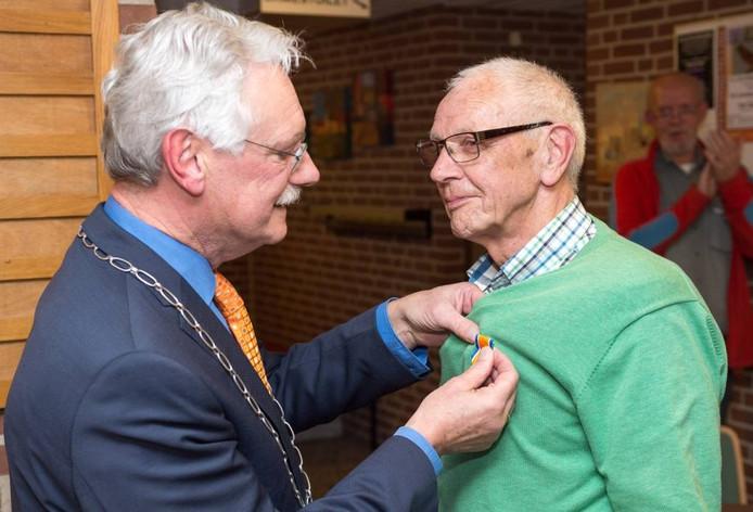 Burgemeester Hans van de Hoeve speldt Theo Huis in 't Veld het lintje op. [FOTOBRON]foto Hans van de Vlekkert