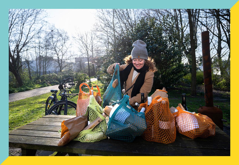 Een klant pakt een borreltas van tafel. Hiske Versprille deelt woensdag 25 maart de tassen uit aan de mensen die een tas hebben besteld.  Beeld Els Zweerink