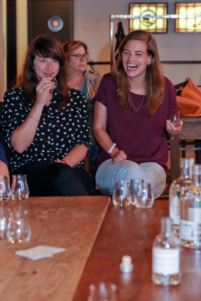 Tijdens de proeverij laten deelnemers zich de Schiedamse gins en jenevers goed smaken.