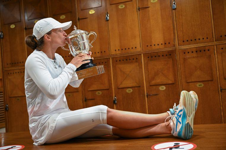 Iga Swiatek kust de trofee in de kleedkamers van Roland Garros.  Ze is de eerste Poolse met een grandslamtitel. Beeld AP