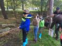 Geblinddoekt met grote zwartgemaakte brillen trekken kinderen langs het spookhuistouw door het bos