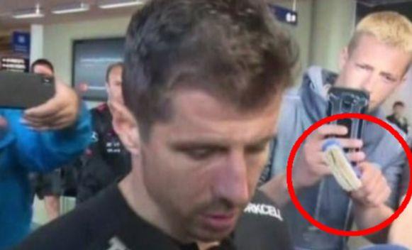 Emre Belozoglu wordt op het vliegveld van Kevlavik aangesproken door iemand met een afwasborstel.
