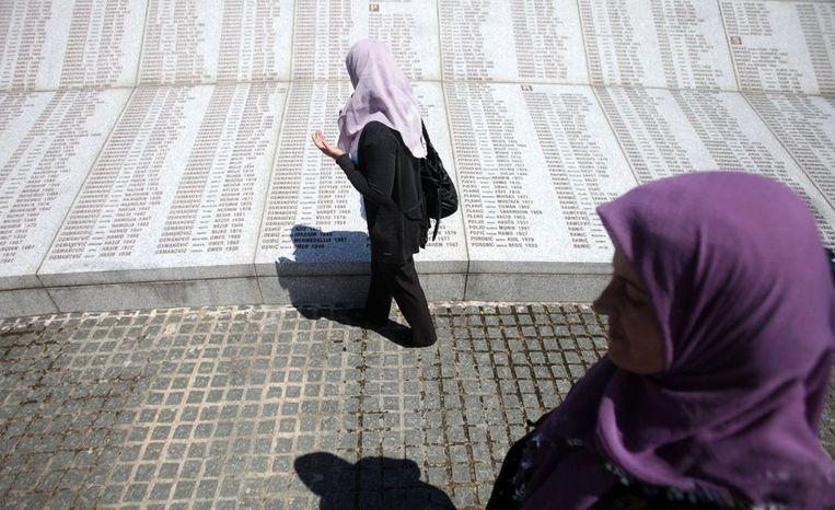 Enkele vrouwen bidden bij een gedenksteen waar de namen van de duizenden moslims in gegraveerd staan die tijdens het bloed in Srebrenica om het leven kwamen. Beeld reuters