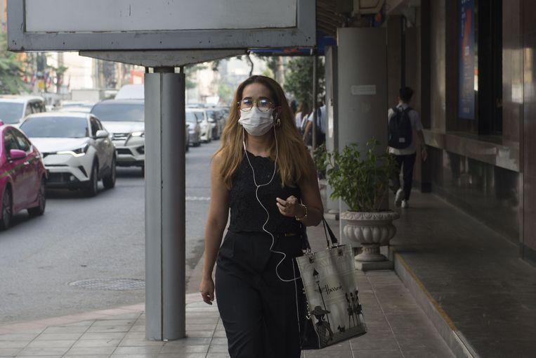 Om zich te beschermen tegen het fijn stof, dragen de inwoners een mondmasker.