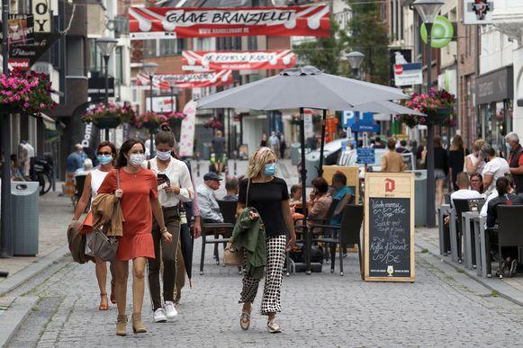 Mensen met mondmaskers wandelen door de Herntalse winkelstraat Zandstraat.