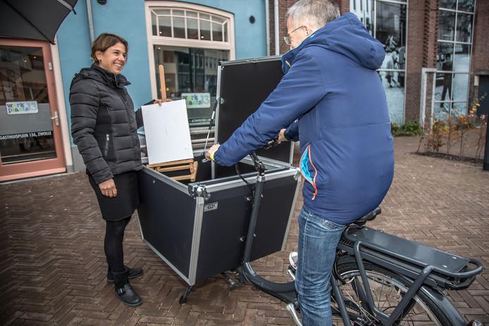 Roos Meijer laat  de verslaggever, die een proefritje maakte, zien hoe makkelijk je veel materiaal kunt vervoeren in een elektrische transportfiets.