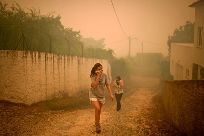 Twee bewoners bedekken hun mond en neus tijdens bosbranden rondom het dorpje Torgal.