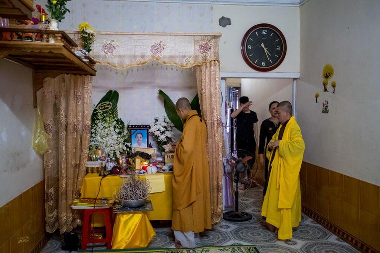 Familieleden en buren van Pham Thi Tra My rouwen met monniken bij een provisorisch altaar in haar woning in Vietnam. De vrouw is waarschijnlijk een van de 39 doden die vorige week in Engeland in een koelwagen zijn gevonden. Beeld Getty Images