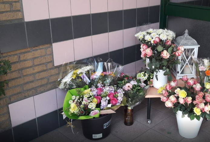 Bloemen bij de flat na het drama.