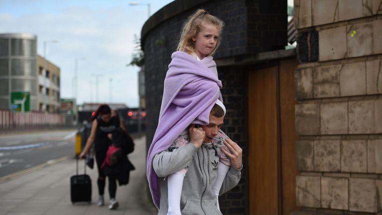 Een meisje wordt weggedragen vlak bij de Manchester Arena. Beeld AFP