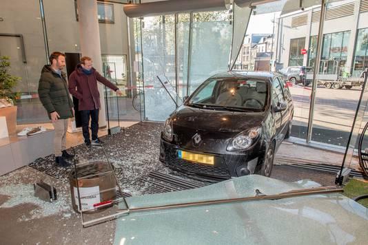 Bram Blijdesteijn (r) bekijkt samen met zijn broer Max bekijkt de schade na de ramkraak op zijn modezaak in Tiel.