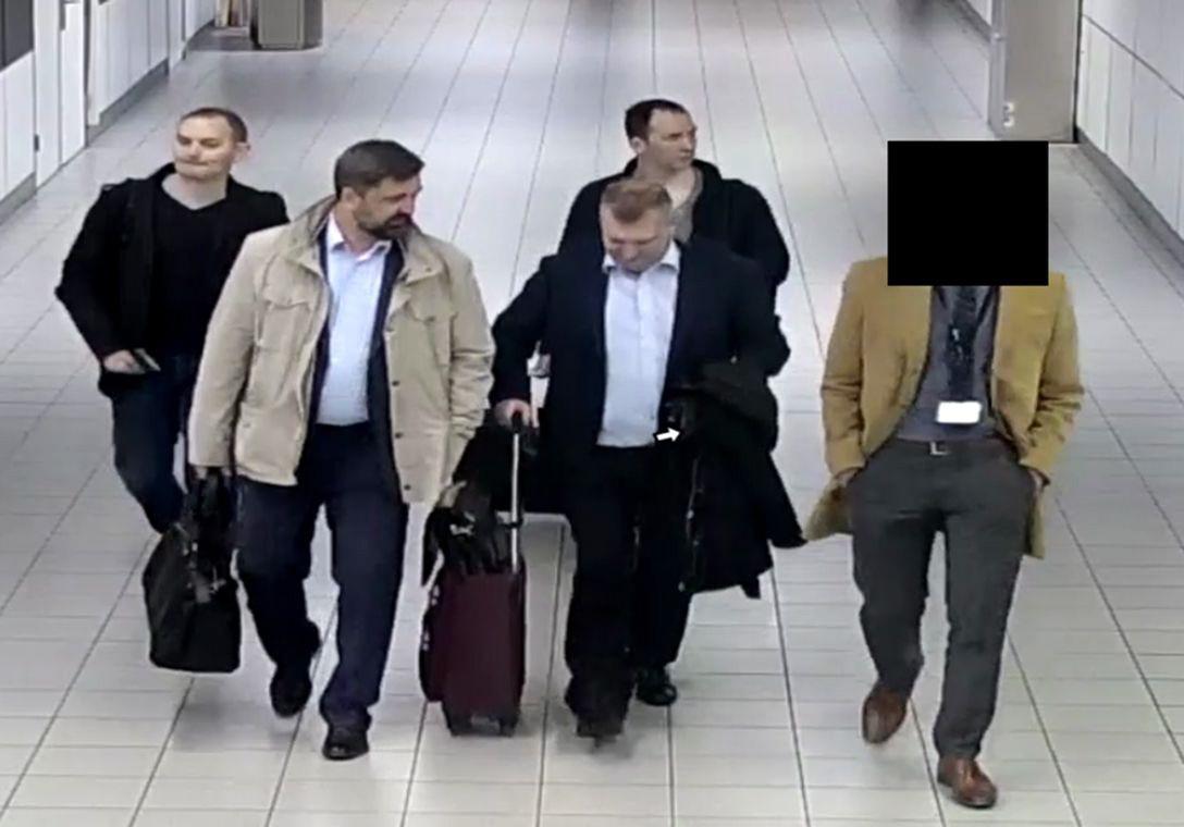 De vier mannen die volgens de MIVD een spionage-operatie in Den Haag opzetten, hier vergezeld door een medewerker van de Russische ambassade op Schiphol.
