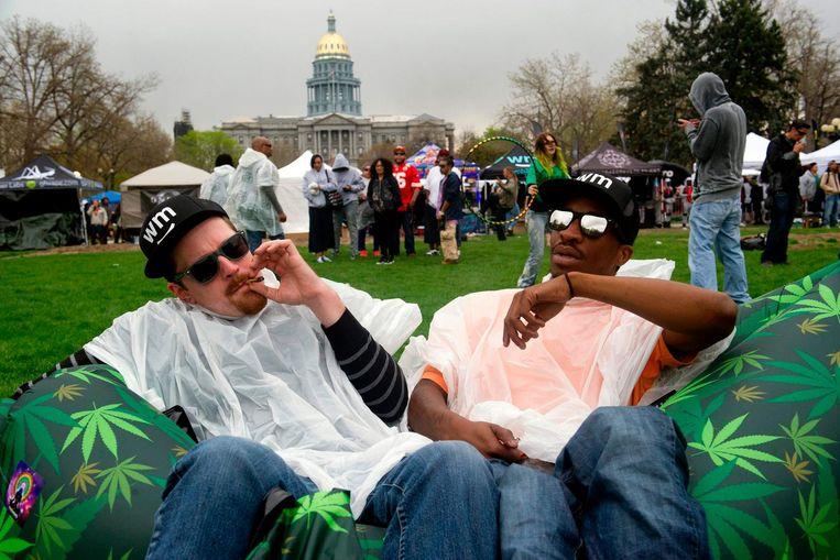 Twee mannen roken een joint op een jaarlijkse bijeenkomst voor de viering van de cannabiscultuur. Beeld afp