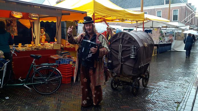Straatmuzikant op de deels veranderde warenmarkt op het Kerkplein