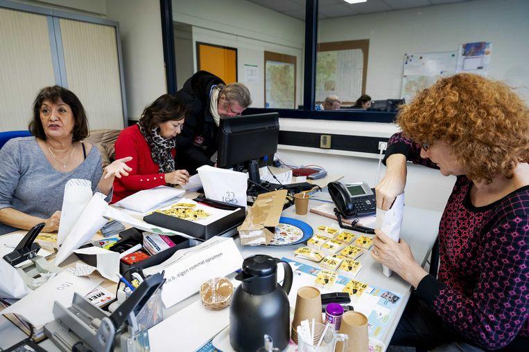 Medewerkers van de Voedselbank Haaglanden pakken bonnen in. Klanten van de Voedselbanken in Zoetermeer, Den Haag en Rijswijk krijgen een supermarktbon in plaats van een voedselpakket nu de voedselbanken in de regio zijn gesloten vanwege het coronavirus.  Beeld ANP