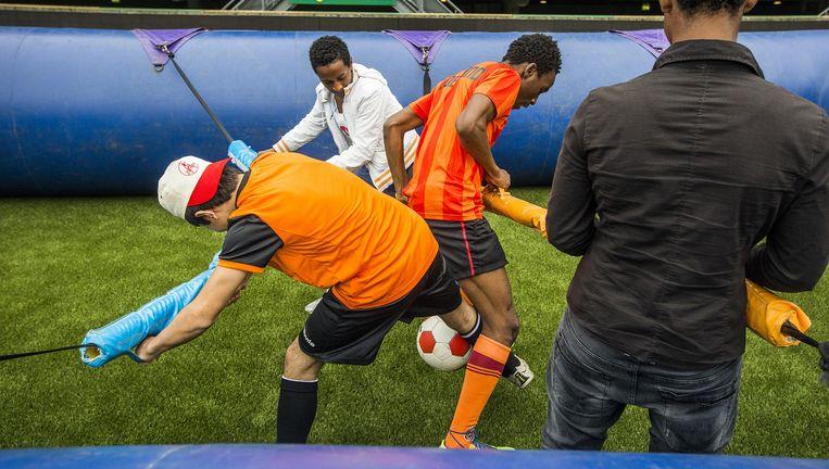 Negentig alleenstaande minderjarige vreemdelingen (amvérs) waren woensdag op bezoek in het stadion vanADODen Haag. Ze konden zich vermaken met een potje 'tafelvoetbal' of het nemen van strafschoppen onder leiding van ADO-spelers. Beeld Jiri Buller