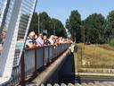Op viaducten boven de A2 verzamelen toeschouwers zich om de colonne te zien rijden.