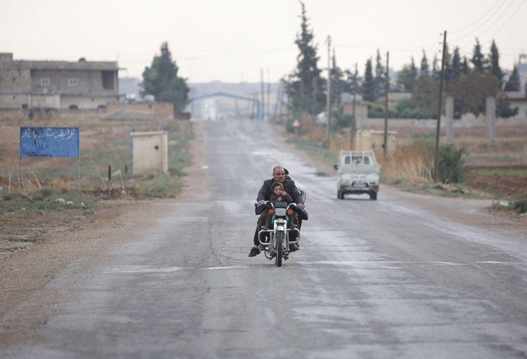 Over verder nagenoeg een uitgestorven weg verlaat een Syrisch gezin per motor Tal Abyad, nabij de Turks-Syrische grens.  Beeld AFP