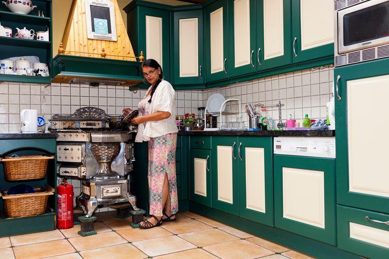Lalla Weiss in haar huis in Best, achter haar antieke plattebuiskachel waarin ze gaspitten heeft  laten bouwen. Beeld Renate Beense
