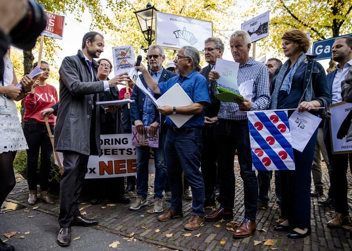 Minister Eric Wiebes van Economische Zaken en Klimaat (VVD) in gesprek met demonstranten.