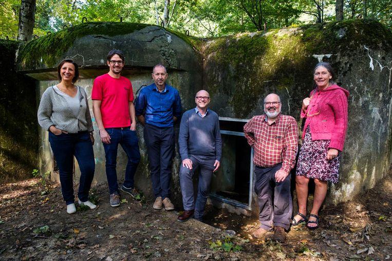 Burgemeester Dirk Bauwens (midden), leden van het schepencollege en mensen van Natuurpunt bij de bunker die nu dienst doet als vleermuizenhotel.