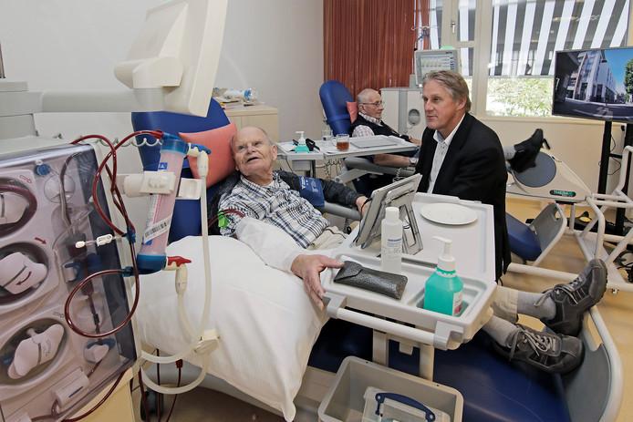 Daan Hollander van Dialysecentrum Ravenstein (rechts) in gesprek met Toon Vos (links). Op de achtergrond is Jan Gubbels aan het fietsen.