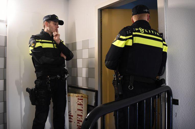 Agenten gaan op bezoek bij een woning in het Oude Westen in Rotterdam. De buurt had geklaagd over de bewoners. Beeld Marcel van den Bergh / de Volkskrant