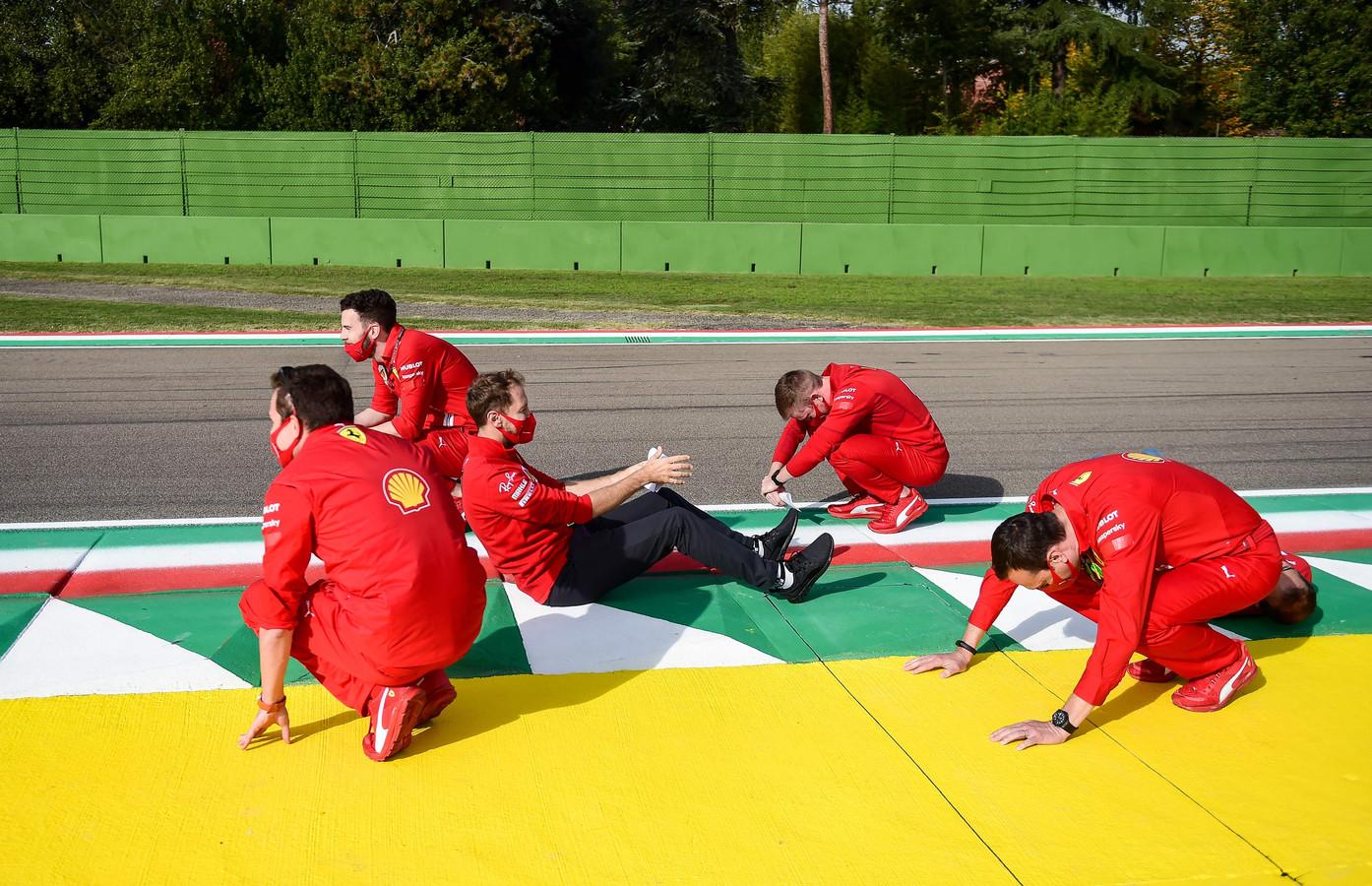 Sebastian Vettel (midden) inspecteert de baan.