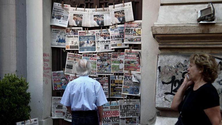 Een man bekijkt de voorpagina's van de kranten in Athene. Beeld AFP