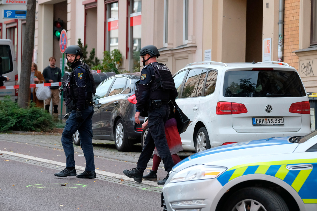 Leden van een speciale politie-eenheid lopen langs een kogelhuls terwijl ze een vrouw uit het afgezette gebied begeleiden.