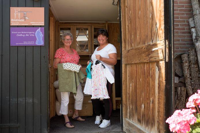 Cathy de Vos en Gisela de Looze bij het naaiatelier van De Vos in Kerkwerve met een paar van de creaties die de Schouwen-Duivelandse club heeft gemaakt of in de maak heeft
