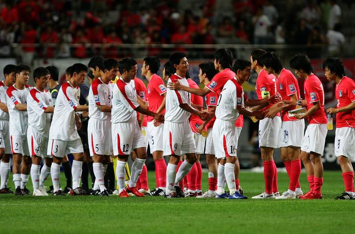 Spelers van Noord-Korea en Zuid-Korea schudden de hand voorafgaand aan de kwalificatiewedstrijd voor het WK in 2010.